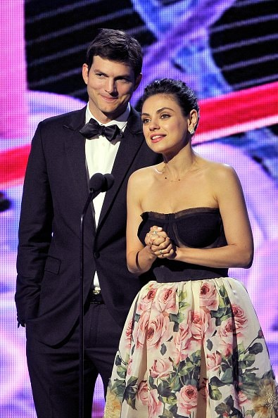 MOUNTAIN VIEW, CA - DECEMBER 03:  Actors Ashton Kutcher (L) and Mila Kunis speak onstage during the 2018 Breakthrough Prize at NASA Ames Research Center on December 3, 2017 in Mountain View, California.  (Photo by Steve Jennings/Getty Images for Breakthrough Prize )